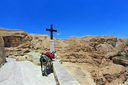 At the roadside donkey tied to a red horse-cloth. A large black cross indicates the way to the temple. Wadi Kelt, the road to the monastery of St. George. Israel