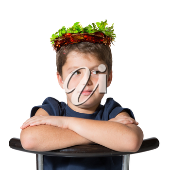 Boy sits astride a chair in carnival wearing a crown of shiny green and red leaf