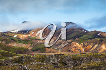 Snow lies in the hollows of multicolored rhyolite mountains. Early summer morning in the National Park Landmannalaugar, Iceland