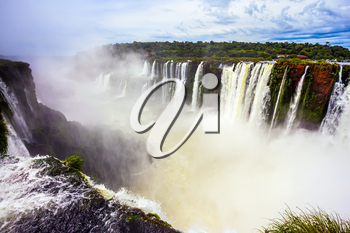 Grandiose waterfalls Iguazu in the rainy season. The most full-flowing waterfall in the world on the Parana River. The Devil's throat /Garganta del Diablo/. Concept of active and extreme tourism