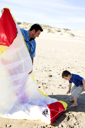 Royalty Free Photo of a Father and Son Getting a Kite Ready on the Beach