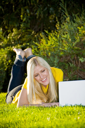 Royalty Free Photo of a Woman Lying in the Grass With a Laptop