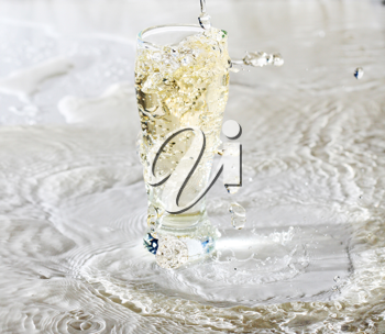 Yelllow drink being poured in a transparent glass with splashes on white