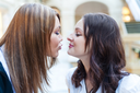 Scenic kiss. Female friends inside the mall. Multicultural friends.
