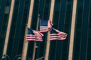 Three US flags against glass wall