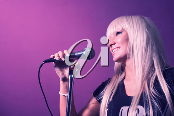 Closeup photo of blond haired nice lady singer on party in night club with microphone karaoke wear black t-shirt on pink color background
