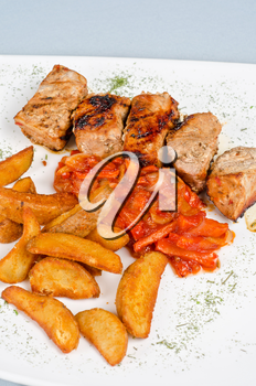 Grilled kebab pork meat with roasted potato and vegetables