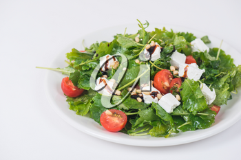 Green salad with vegetables: greens, arugula, tomato, cheese, pine nuts and sauce