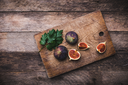 Tasty Figs on chopping board and wooden table. Autumn season food photo