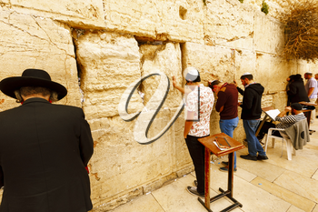Jerusalem, Israel-March 14, 2017: Jews pray at The Western Wall - the holiest place where Jews are permitted to pray, though it is not the holiest site in the Jewish faith, which lies behind it, on Te