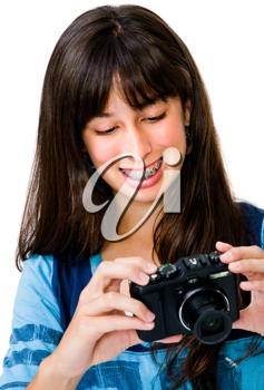 Close-up of a teenage girl photographing with a camera and smiling isolated over white