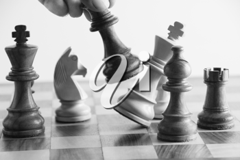 Person's hand defeating a king in the game of chess
