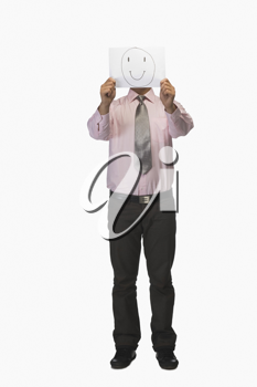 Businessman holding a piece of paper in front of his face with a smiley on it