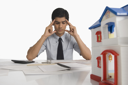 Real estate with head in hands sitting near a model home