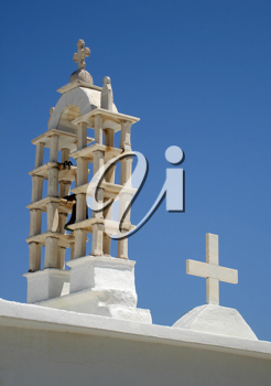 The belltower and cross on a Greek Church against clear blue sky