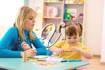 Royalty Free Photo of a Teacher and a Little Girl Colouring
