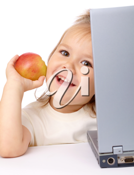 Royalty Free Photo of a Little Girl at a Laptop Holding an Apple