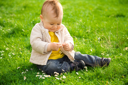 Royalty Free Photo of a Little Boy in a Meadow Holding a Daisy