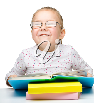 Cute cheerful little girl reading book wearing glasses, isolated over white