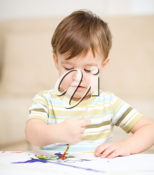 Portrait of a cute little boy playing with paints