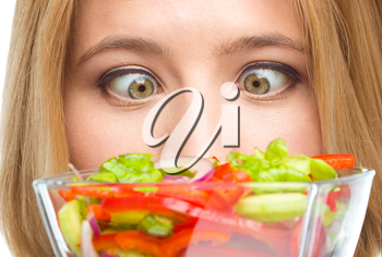 Woman is looking at salad crossing her eyes, isolated over white