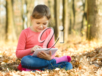 Little girl is reading from tablet while sitting on yellow autumn leaves, outdoor shoot