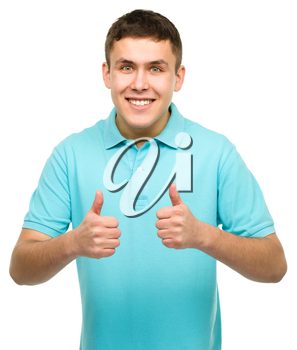 Cheerful young man showing thumb up sign using both hands, isolated over white