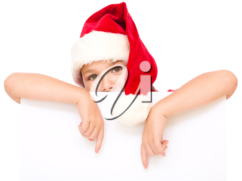 Little girl in santa hat is holding blank board and pointing to it using index finger, isolated over white
