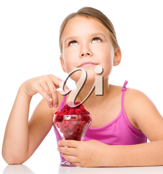 Happy little girl eats raspberries and looking up, isolated over white