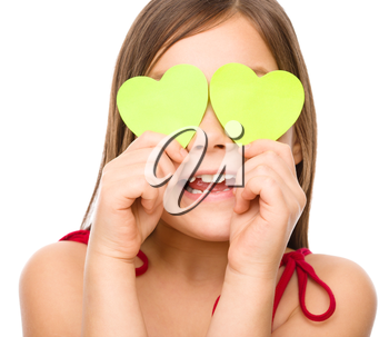 Little girl is holding hearts over her eyes, valentine concept, isolated on white