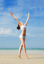 Royalty Free Photo of a Woman at the Beach With Her Arms Outspread