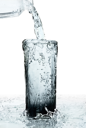 glass of a water with overflow on white background
