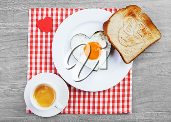 Fried egg  in heart shape  and toast with love message.Breakfast for a loved one