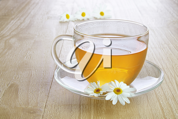 Camomile tea in glass cup on vintage wooden table