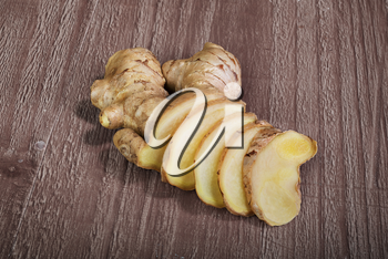 Ginger root slices on vintage wooden background