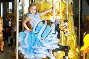 Pretty little girl in blue dress riding on a carousel