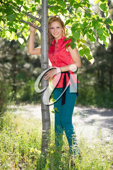 Smiling blond woman in red blouse and blue jeans posing near the tree