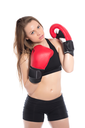 Portrait of young blonde posing in black sportswear with red boxing gloves. Isolated on white