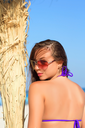 Pretty young woman in sunglasses posing on the beach