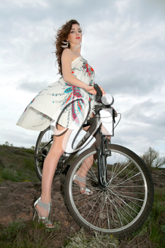 Sexy curly brunette in white dress with flower posing on the bike