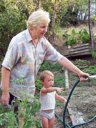 Grandmother and grandson in the garden watering