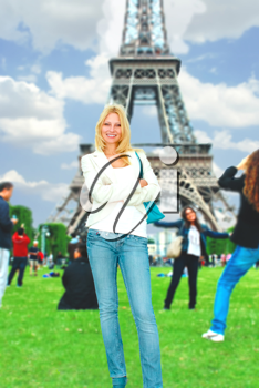 Girl with another tourists is posing against  backdrop of Eiffel Tower
