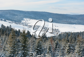 Royalty Free Photo of a Snowy Village in a Valley Between Forested Mountains