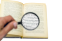 Royalty Free Photo of a Book Under a Magnifying Glass
