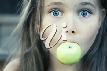 Royalty Free Photo of a Surprised Young Girl Eating an Apple
