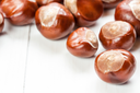 Fruit chestnut on a white wood background with copy-space