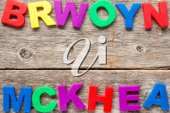 Old wooden background with multicolored toy letters
