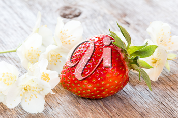 Single strawberry and white flowers on wooden background