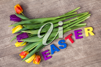 Lettering EASTER and bouquet of colorful tulips