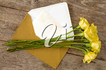 Yellow roses and love letter or note card with golden envelope
